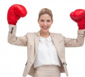 A smiling businesswoman holding boxing gloves on white backgroun