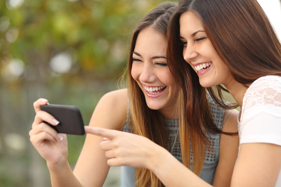 Two Funny Women Friends Laughing And Sharing Media In A Smart Ph