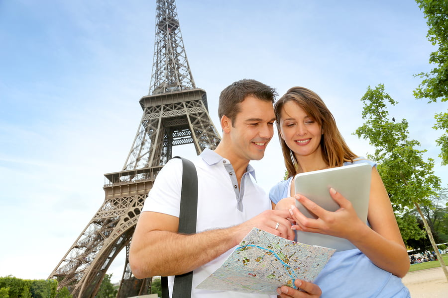 Tourists using an iPad in front of the Eiffel tower
