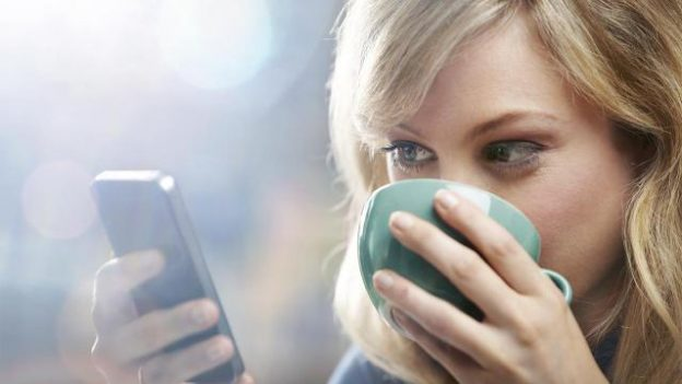 woman smiling drinking coffee looking at phone