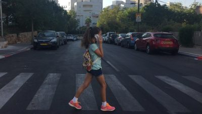 a-girl-crossing-the-street-while-talking-on-her-cell-phone-photo-by-einat-paz-frankel