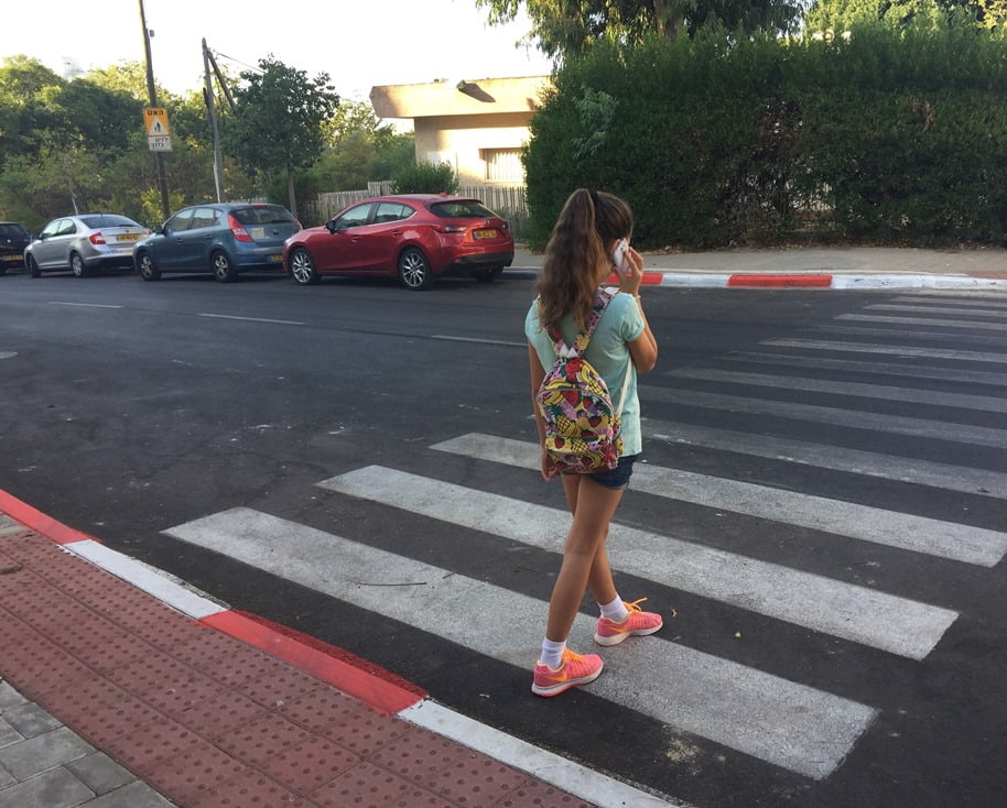 a-girl-crossing-the-street-while-talking-on-her-smartphone-photo-by-einat-paz-frankel