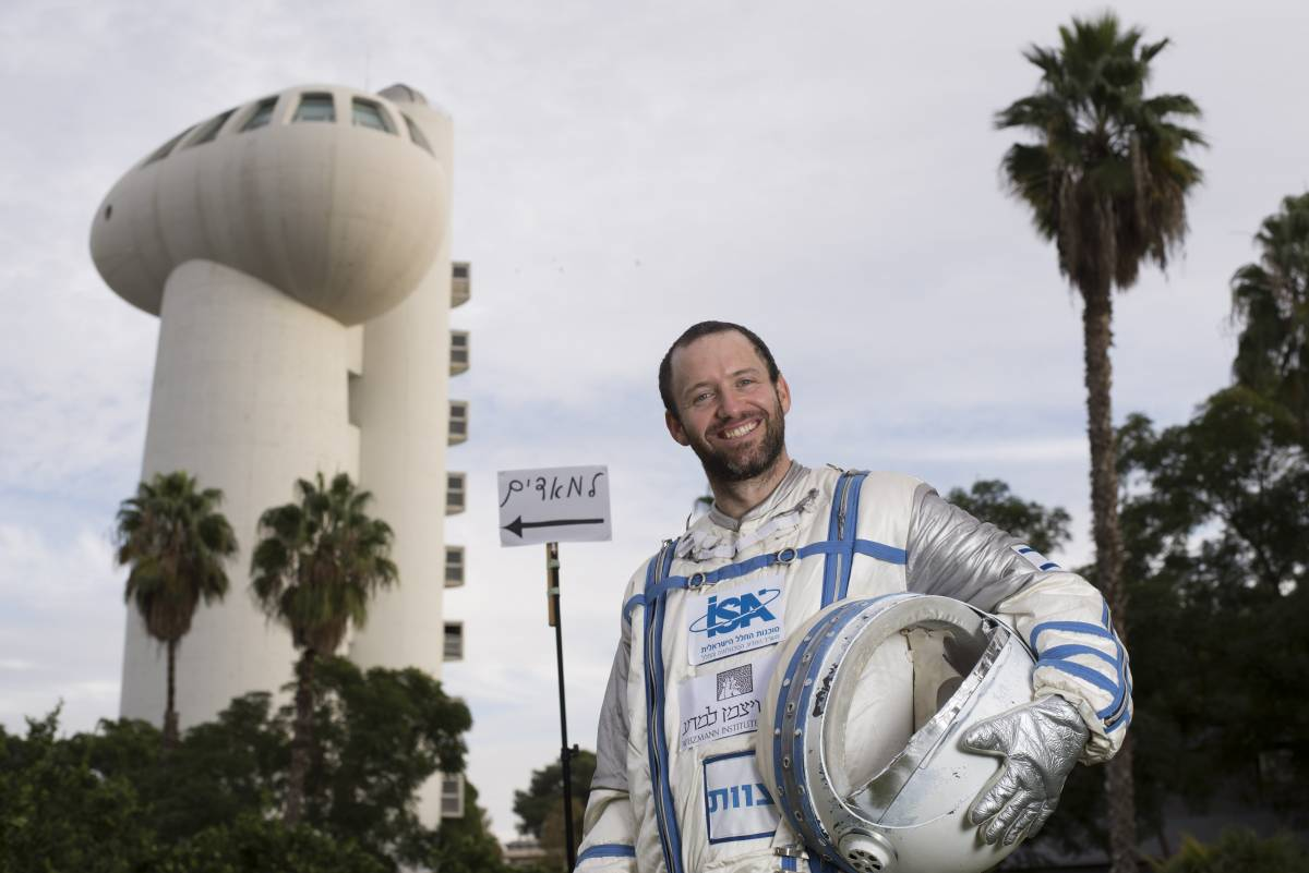"""Roy Naor next to a sign in Hebrew which reads """"To Mars"""". Courtesy"""