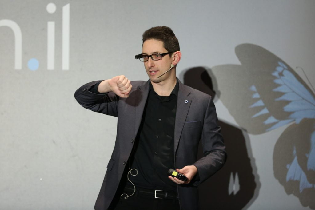 Eliav Rodman is not wearing a watch, but the OrCam MyEye attached to his glasses recognizes his wrist and tells him the time, At the Digital Health IL conference in Tel Aviv on January 23, 2018. Photo by Shauli Landner