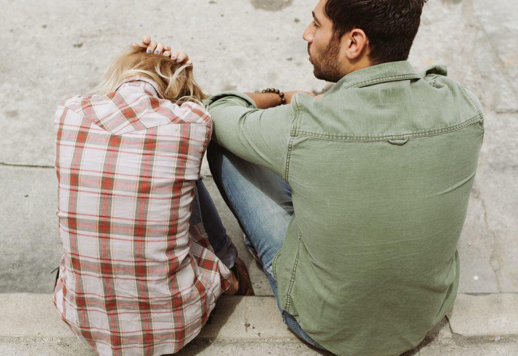 A woman and man on a sidewalk. Photo via Pexels