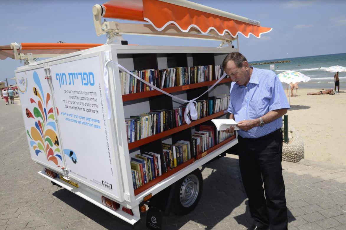 Tel Aviv-Jaffa Mayor Ron Huldai checks out the lending library at the beach. Courtesy.
