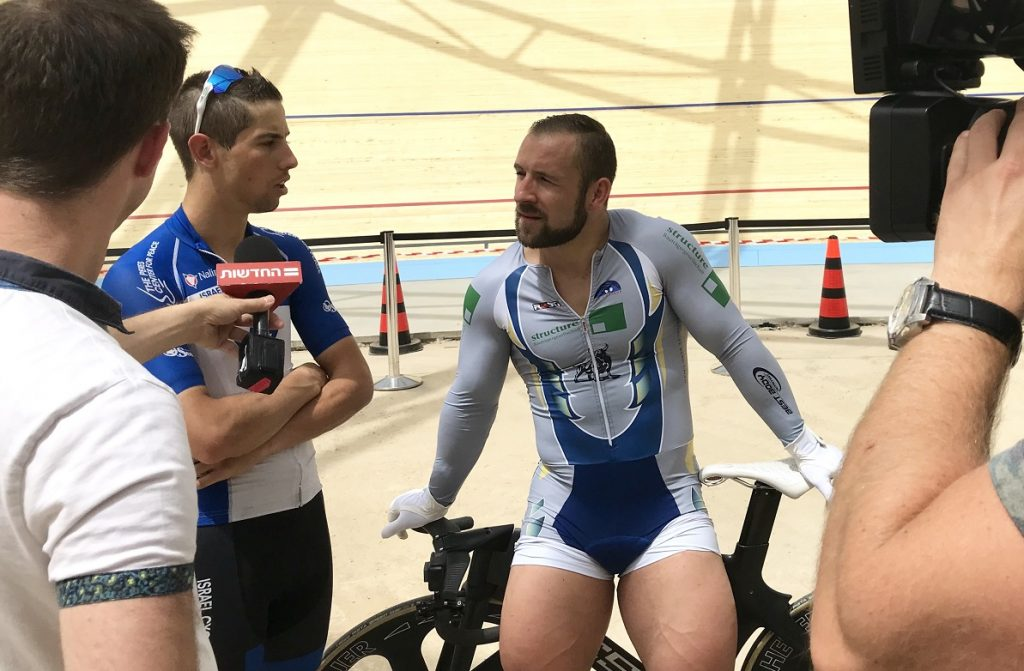 Journalists interview German track cyclist Robert Förstemann, center, and Israel Cycling Academy's Roy Goldstein at the Velodrome in Tel Aviv, May 1, 2018. Photo by Viva Sarah Press