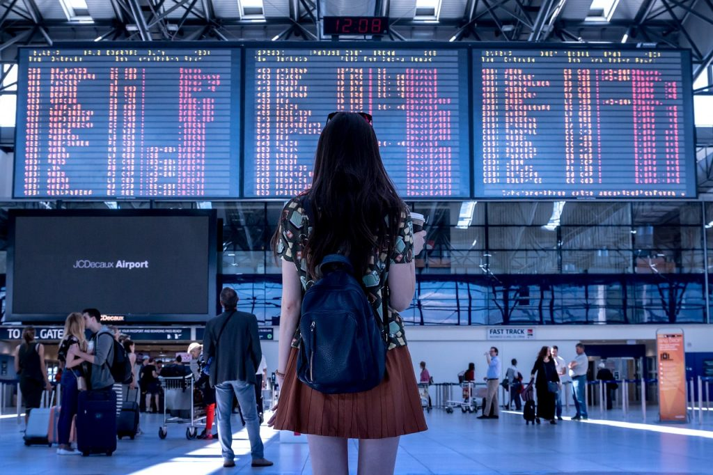 An illustrative photo of a woman standing in an airport. Photo by Pexels