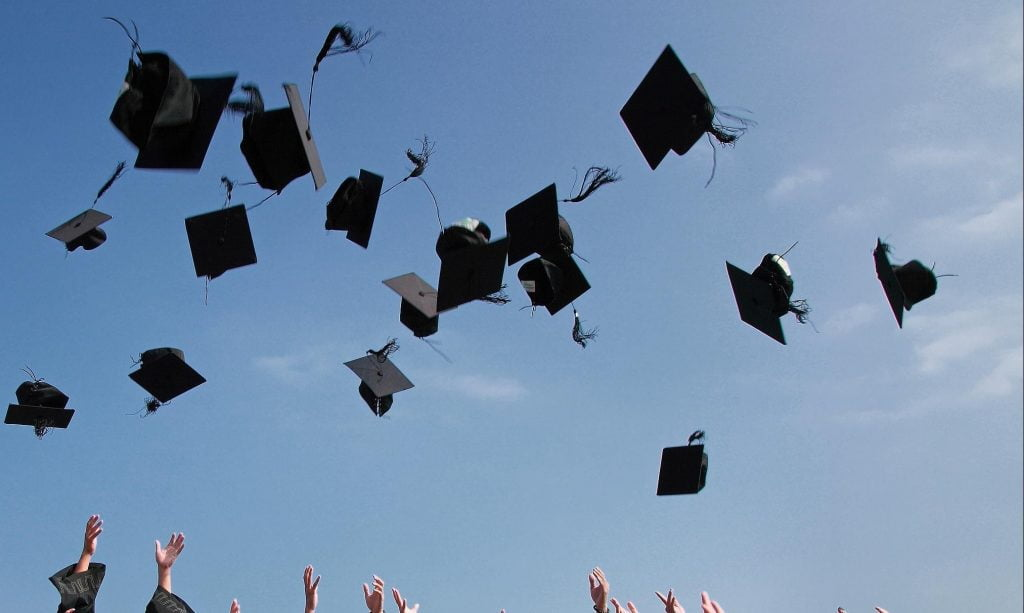 Graduation caps in the air. Illustrative photo by Pexels