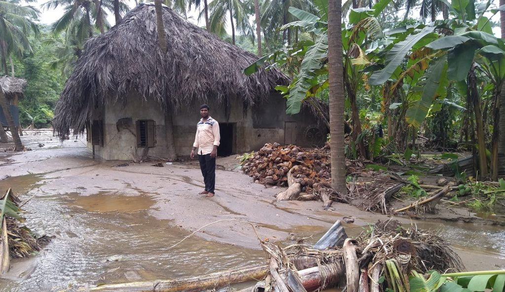 A man standing outside a home near Malampuzha Dam in Kerala, India. Photo via Flickr