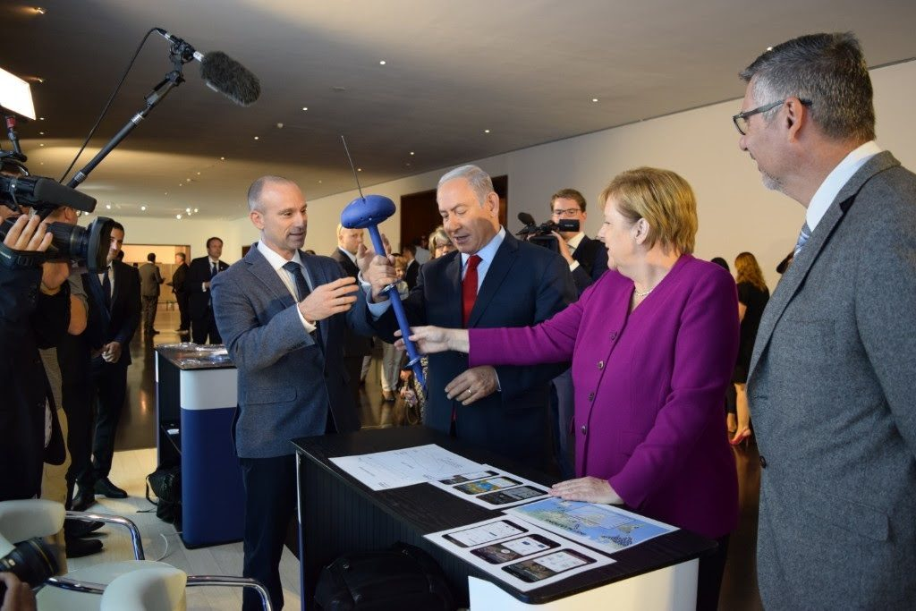 CropX CEO Tomer Tzach presents the company's soil sensor to Israeli Prime Minister Benjamin Netanyahu and German Chancellor Angela Merkel. Courtesy