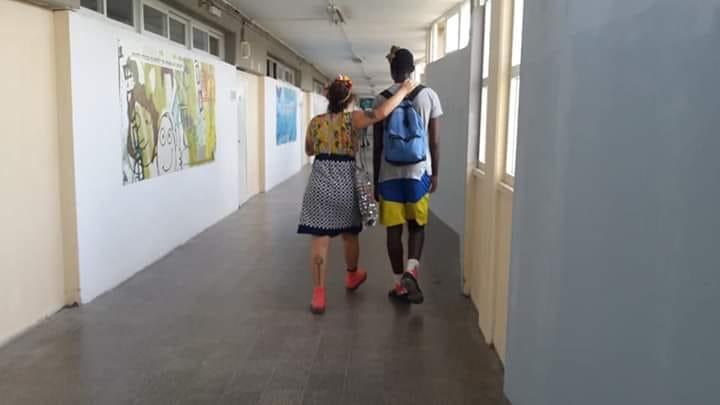 An educational clown walks in a hallway with an Israeli high school student. Courtesy