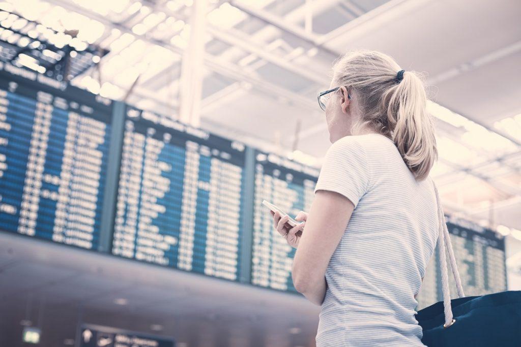 "A woman holding a phone in an airport. <a href=""http://dep.ph/v/zj761t-bsat0"" target=""_blank"">Deposit Photos</a>"