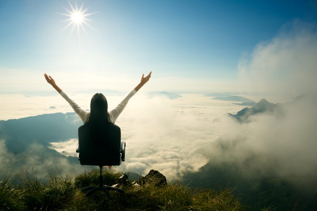 A woman sitting on a mountain top. Illustrative. Deposit Photos