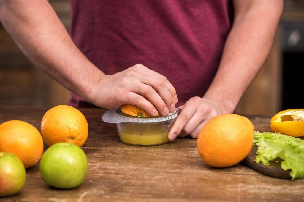 Squeezing orange juice.  Deposit Photos