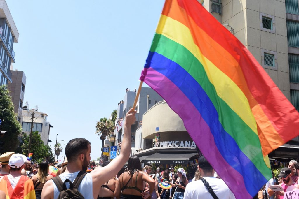 A person waving a pride flag at the annual Tel Aviv Pride Parade, June 14, 2019. Photo by Anjali Berdia