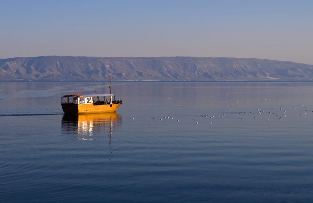 """A boat floats on the Sea of Galilee . <a href=""""https://depositphotos.com/stock-photos/sea-of-galilee.html?filter=all&qview=9569778"""" target=""""_blank"""" rel="""