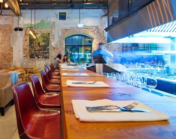 Dinner in a modern open kitchen restaurant in Tel Aviv. Deposit Photos