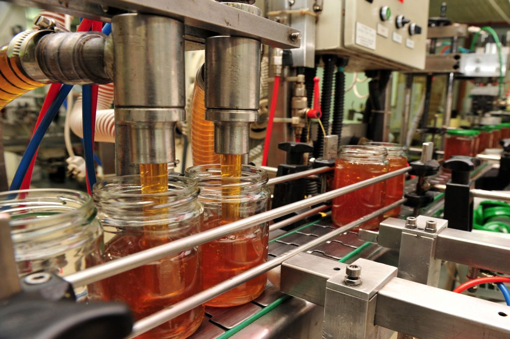 A machine fills jars with honey in a production line in Yad Mordevhai, Israel. Deposit Photos