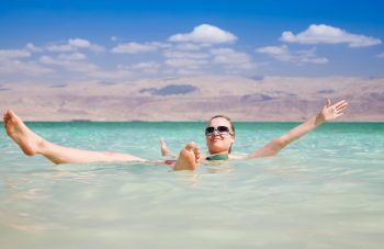 A woman floating in the Dead Sea. Illustrative. Deposit Photos