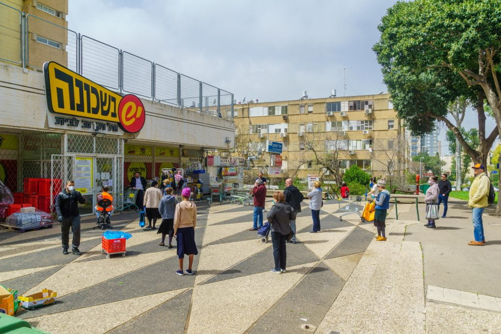 People follow the social distancing rules while waiting outside a supermarket in Haifa, Israel. March 2020. Deposit Photos