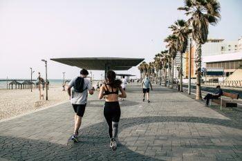 Joggers on the Tel Aviv promenade in April 2020 during the global pandemic. Deposit Photos